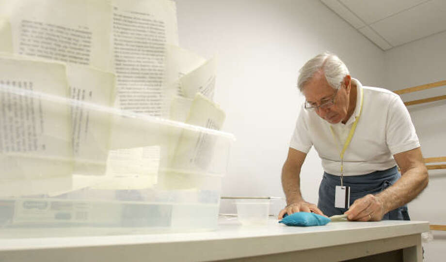 Charlie Arbore uses a special tape to repair torn pages in an 1821 volume of The Conquest of Granada for the special collections section at the Houston Public Library downtown. The retired Shell Oil engineer took up book restoration in 1975. Photo: Nick De La Torre, Chronicle