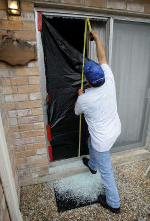 Un trabajador mide una puerta para colocar un nuevo vidrio en una casa del suroeste de Houston que fue objeto de un reciente robo a través del patio. Esa zona de la ciudad es la que sufre de una mayor concentración de robos. Photo: Melissa Phillip, Houston Chronicle