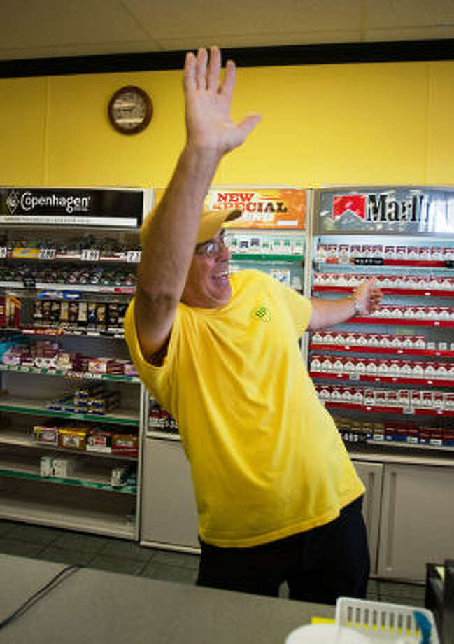 Wearing BP's signature yellow T-shirt, Keith Fayard acknowledges a customer at the gas pumps while working the register at his family's BP station in Biloxi, Miss. Photo: Smiley N. Pool, Chronicle