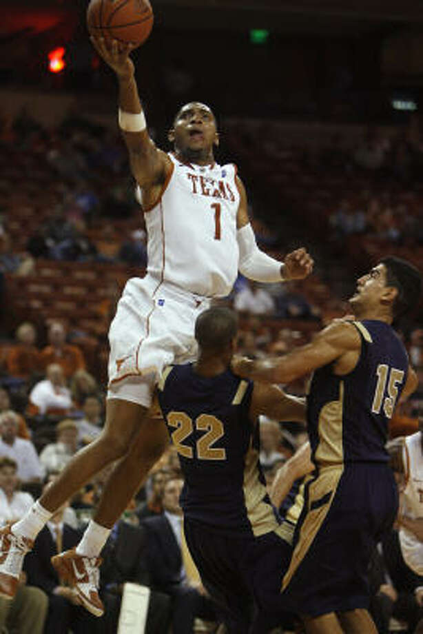 Texas' Gary Johnson shoots over Navy's Isaiah Roberts, left, and Romeo Garcia during the second half. Johnson had 17 points in 28 minutes of action. Photo: Deborah Cannon, AP
