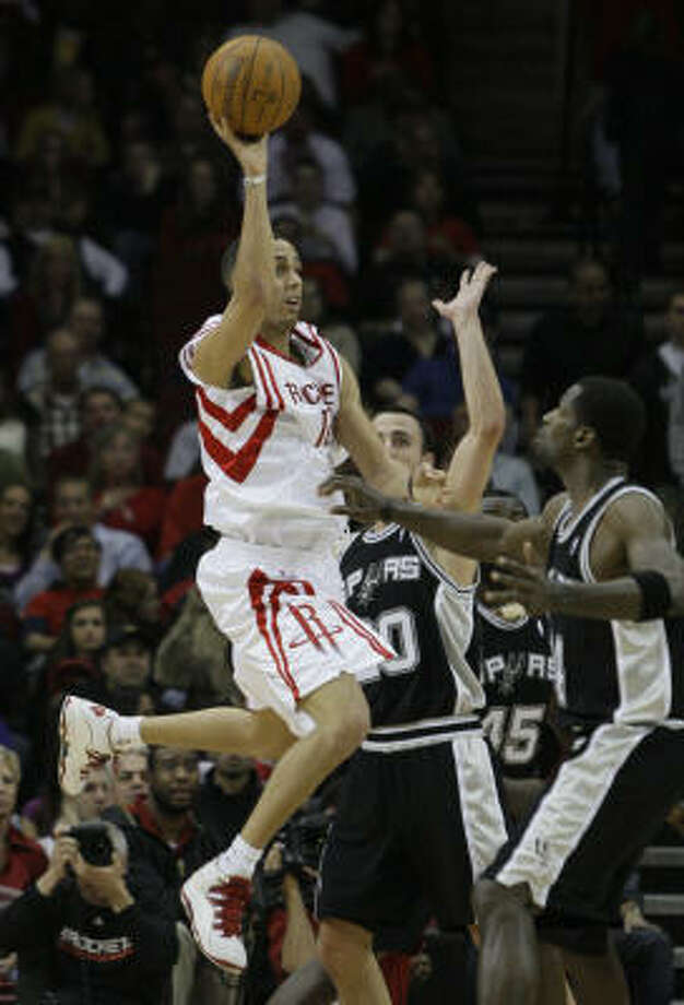 Kevin Martin passes the ball over Spurs guard Manu Ginobli (20) and forward Antonio McDyess. Photo: Pat Sullivan, AP
