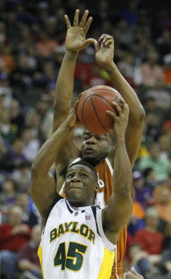 Baylor guard Tweety Carter pulls down a rebound in front of Texas guard Justin Mason. Photo: Charlie Neibergall, AP