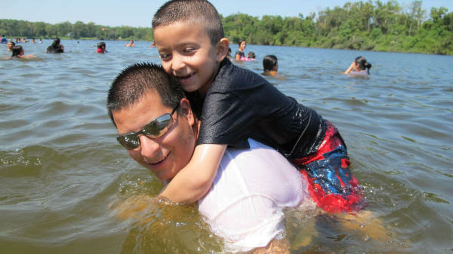 Robert Gonzalez, of Highlands, and his son, Jose, 7, enjoy a Sunday outing in the Banana Bend section of the San Jacinto River, where there have been seven drownings this year. Signs on the area's private beaches warn swimmers they are on their own. Photo: Melissa Phillip, Chronicle