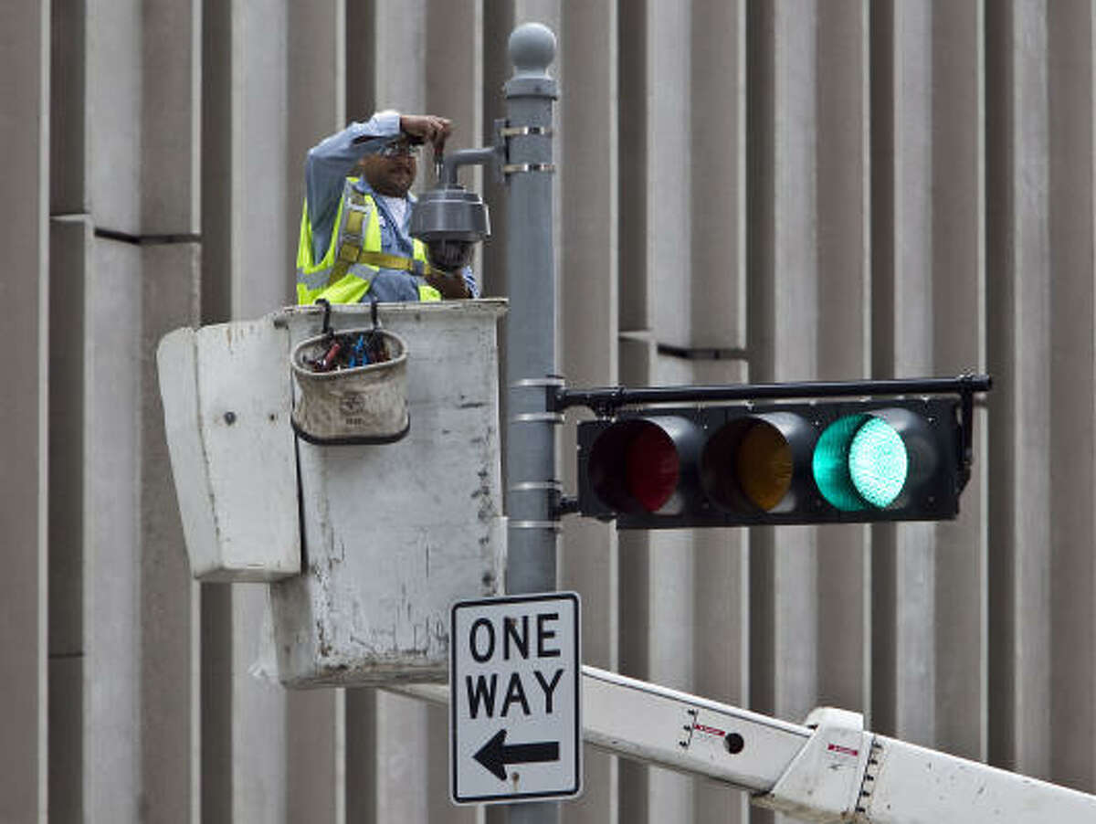 A worker installs a surveillance camera at Rusk and Milam on Wednesday. Some Houstonians say they find the idea a comfort, while other worry about Big Brother or the cost of the system.