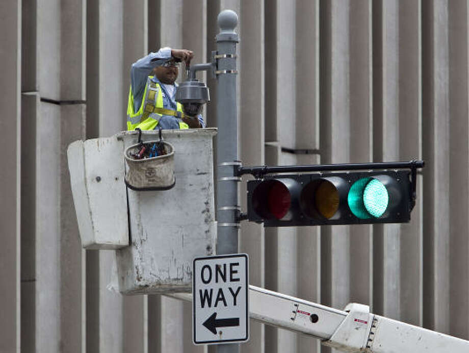 A worker installs a surveillance camera at Rusk and Milam on Wednesday. Some Houstonians say they find the idea a comfort, while other worry about Big Brother or the cost of the system. Photo: James Nielsen, Chronicle