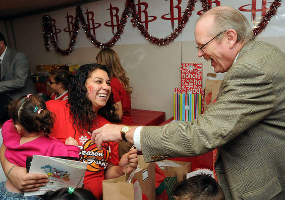 Houston Chronicle Publisher Jack Sweeney hands gifts to Gabrielle Infante and her daughter, Janelle Fults. Photo: Dave Rossman, Chronicle