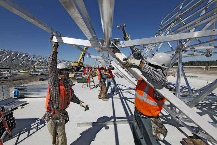 Workers assemble the pipeline that will move solar-heated synthetic oil through the solar thermal mirror assemblies under construction at the FPL Group's Martin Next Generation Solar Energy Center in Indiantown, Fla. Photo: John Van Beekum:, New York Times