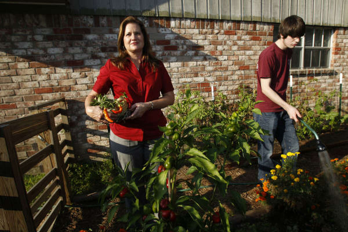 Linda Costanzo is shown with her son Michael, 19, in the garden at the home she is fighting to keep in Conroe. She said she believes she's a victim of a bureaucratic misstep.