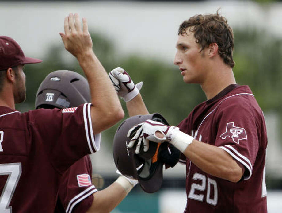Texas A&M's Adam Smith, right, is congratulated by teammates after hitting a two-run home run against Miami in the fourth inning. Photo: Alan Diaz, AP
