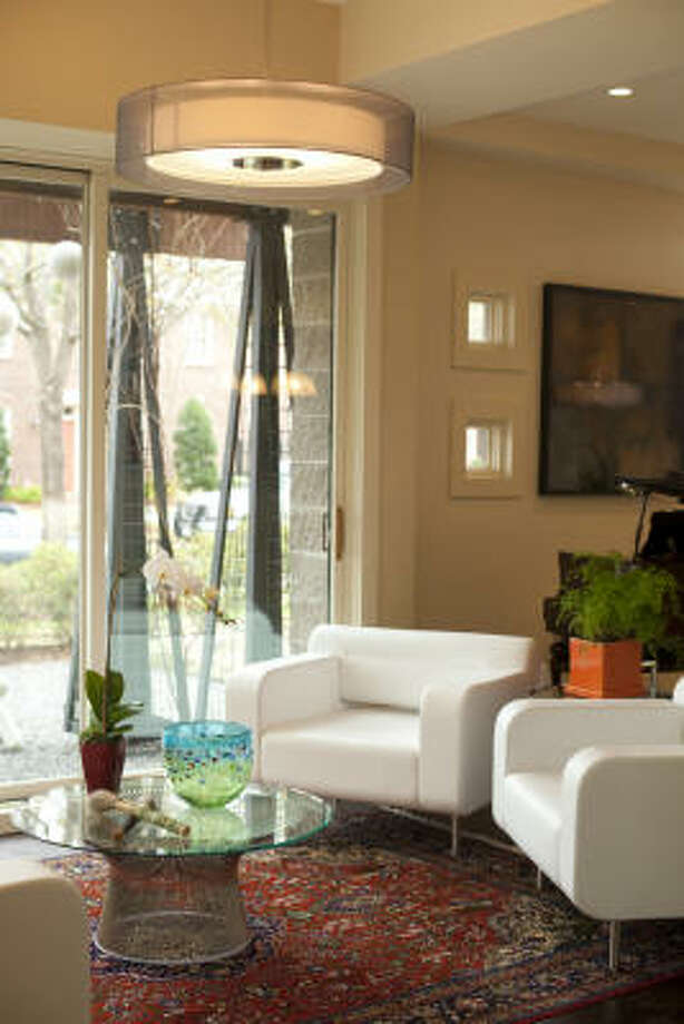 The Orly leather sofa and chairs were designed by Patrick Norguet. Homeowners Denmon Sigler and Peter Chok acquired one chair through a charity auction and liked it so much that they purchased a second and the matching sofa. The coffee table, designed by Warren Platner, is from Design Within Reach. Robert Held, a Canadian glass artist, created the bowl. The antique brushes are for Asian calligraphy. Photo: Jill Hunter