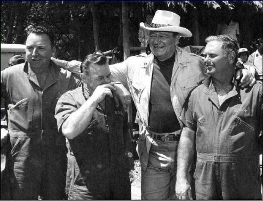"E.O. ""Coots"" Matthews, left, stands with his mentor Paul ""Red"" Adair, screen star John Wayne and Asger ""Boots"" Hansen during the filming of Wayne's 1968 movie Hellfighters Photo: Boots & Coots International Well Control"