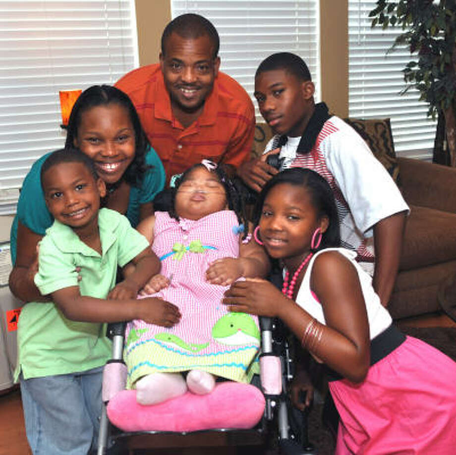 SURROUNDED BY LOVE: Kayla Jolivet, 3, center, who has cerebral palsy is surrounded by her family clockwise from left: brother Kyndl, 4, mother LaTonya, father Thomas, brother Kuadetric, 15, and sister Kuashaya, 12. The Jolivet family is involved with the Houston Hospice Butterfly Program, which provides support to families with terminally ill members. Photo: Ernie Chan, For The Chronicle