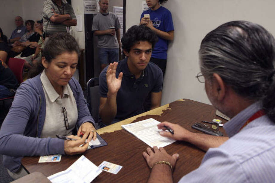 Andrew Jasso,18, swears to the veracity of his passport application Monday as his mother Esthela Jasso writes a check to clerk Hector Casalas at the post office on Perrin-Beitel. Passports for adults jump to $135 today; renewals will cost $110. Photo: JOHN DAVENPORT, SAN ANTONIO EXPRESS-NEWS