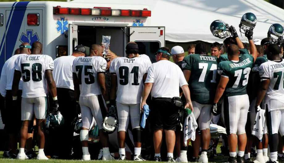 Philadelphia Eagles players and coaches including head coach Andy Reid, center in white hat, gather around defensive tackle Mike Patterson as he is put into an ambulance after he had a seizure during an NFL football training camp practice at Lehigh University Wednesday, Aug. 3, 2011 in Bethlehem, Pa. (AP Photo/Alex Brandon) Photo: Alex Brandon, STF / AP