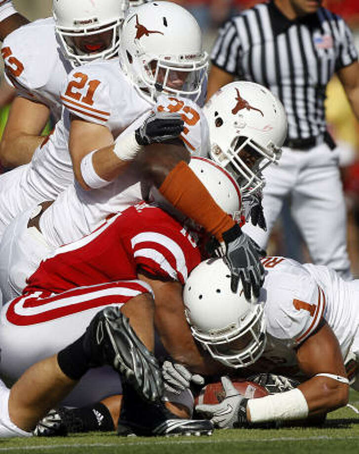 Texas linebacker Keenan Robinson (1) wrestles a fumble away from Nebraska running back Roy Helu Jr. Photo: AP