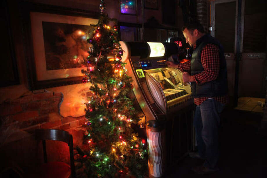 """I love this jukebox,"" says Stephen Bridges, a native Houstonian who lives in San Francisco. Bridges, who is home for the holidays, likes to visit La Carafe, among other Houston locales. Photo: Mayra Beltran, Houston Chronicle"