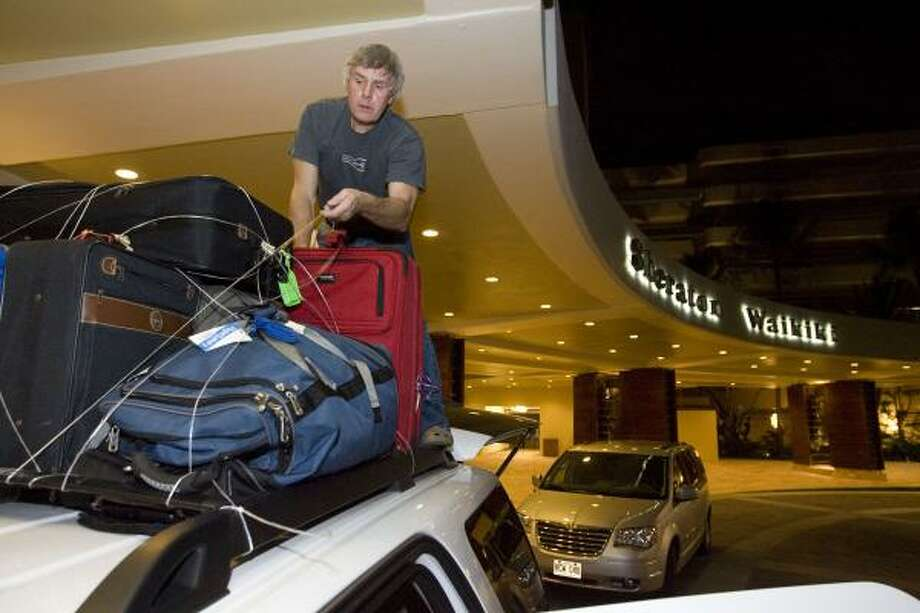 Dean Collins, of Anderson, S.C., ties down his luggage on the roof of a sport utility vehicle in front of a hotel early Saturday in the Waikiki area of Honolulu. Photo: Eugene Tanner, Associated Press
