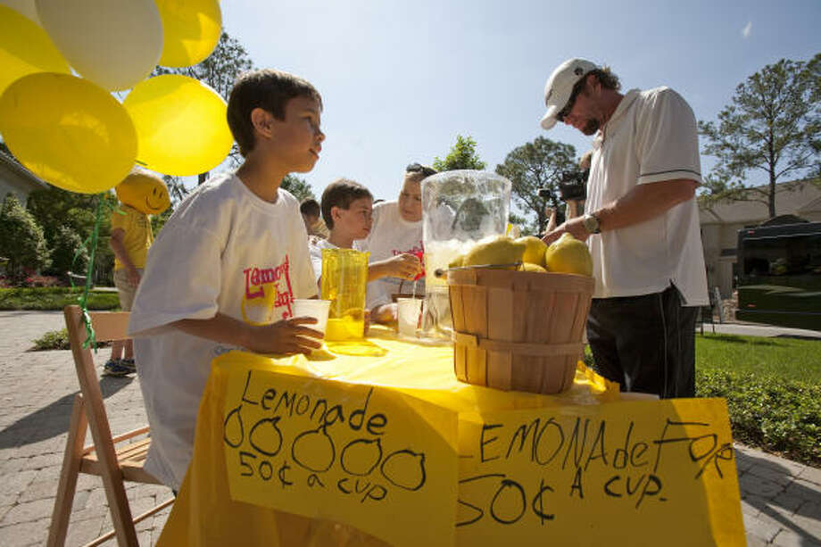 Ryder Hammond, left front, 11, and his twin brother, Wyatt, serve Astro legend Jeff Bagwell a glass of lemonade at a stand they put up in front of one of John Daugherty Realtors' listed properties Sunday in Bellaire. Photo: Nick De La Torre, Chronicle
