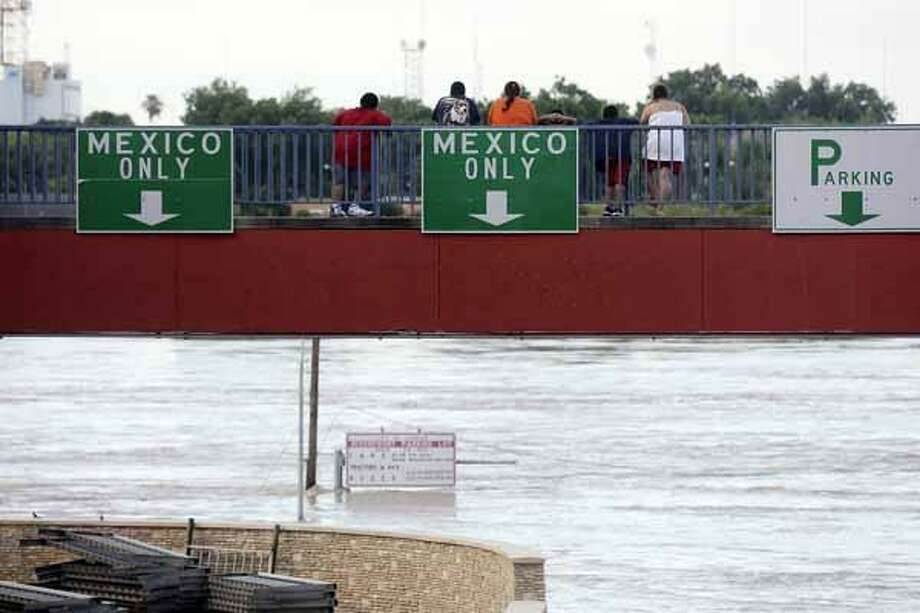 Onlookers watch the rising Rio Grande near International Bridge I in Laredo. Photo: EDWARD A. ORNELAS, SAN ANTONIO EXPRESS-NEWS