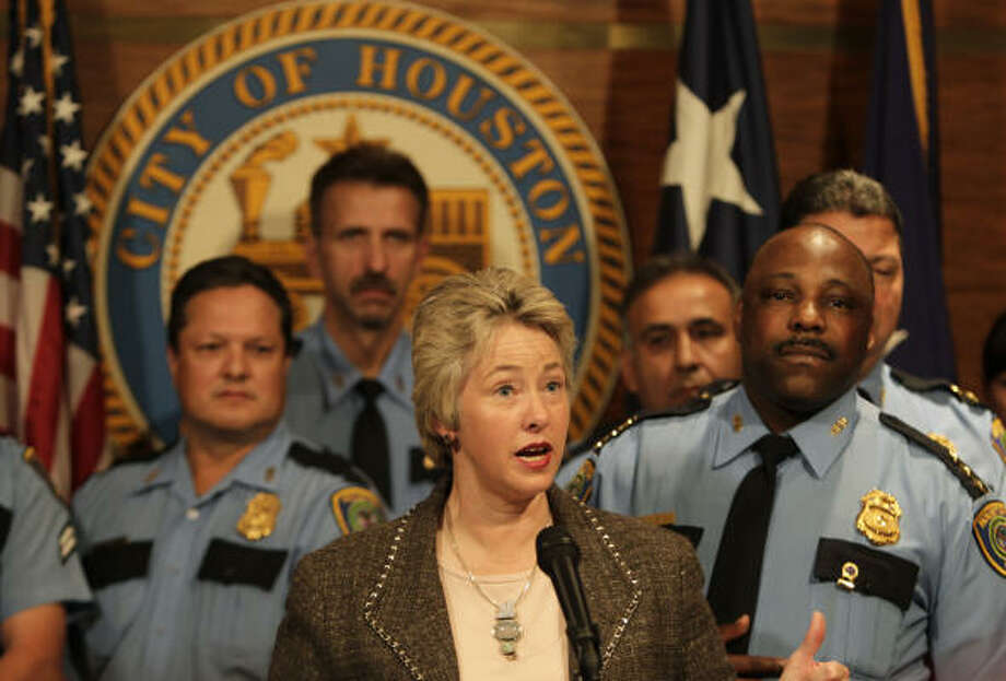 "Mayor Annise Parker, along with HPD Assistant Chief Michael Dirden, right, and other officers, discusses the city's plans for the new officers. ""We will spend these dollars wisely,"" she said. Photo: Karen Warren, Chronicle"