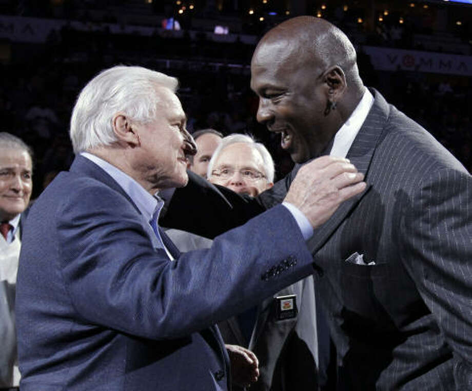 Charlotte Bobcats owner Michael Jordan, left, embraces former North Carolina coach Dean Smith, right, at halftime of the Bobcats-Toronto Raptors game in Charlotte on Tuesday night. Jordan was inducted into the North Carolina Sports Hall of Fame during a halftime ceremony. Photo: AP