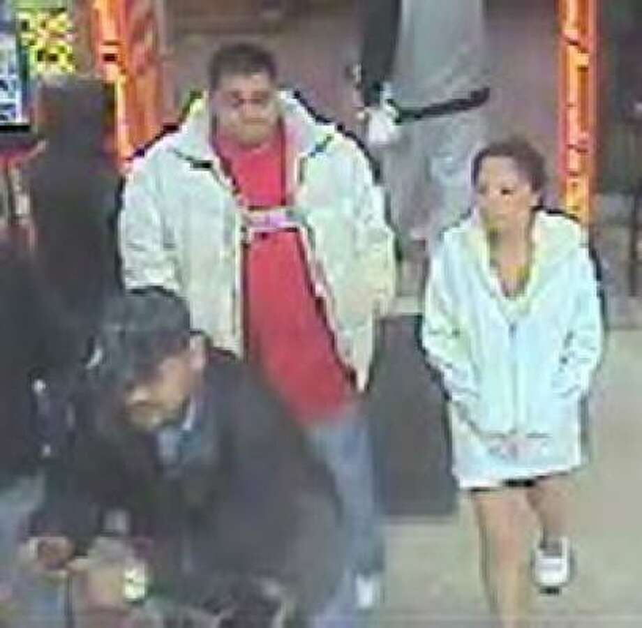 A surveillance camera photographed three people using a credit card taken during a violent robbery in December. Police are seeking three men who they say committed the robbery. Photo: Surveillance Photo