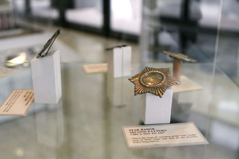 Badges from different years fill display cases at the new Houston Police Department Museum at 1200 Travis. Visitors can see exhibits and buy HPD caps and T-shirts in a gift shop. Photo: Yasmeen Smalley, Chronicle