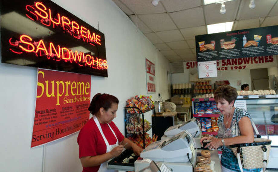 Maria Ramirez, a cashier at Supreme Sandwiches, helps longtime customer Mindy Laird. Supreme Sandwiches, like other mom and pop stores, can compete with chains because of its low prices. Photo: John Jiles:, Houston Chronicle