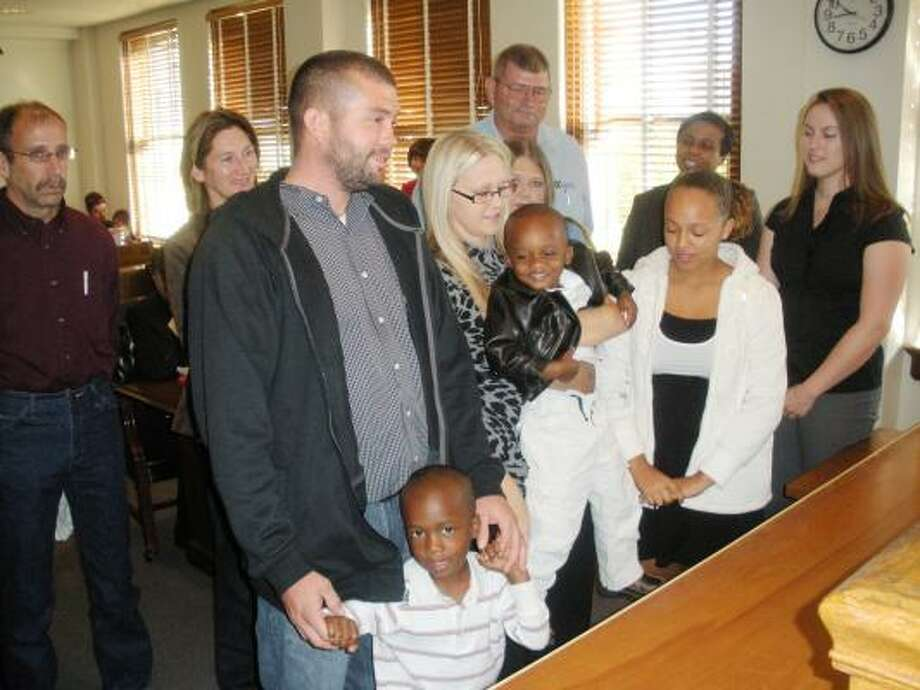 B.J. POLLOCK PHOTOS: FOR THE CHRONICLE BIG HAPPY FAMILY: Standing before state District Judge Ron Pope on Adoption Day last month at the Fort Bend County Courthouse are, in front, from left, adoptive dad B.J. Shelton, son Jaden Shelton, adoptive mom Fallon Shelton, son Jaylon Shelton, maternal grandmother Donna Johnson, daughter Asia Kucera and CPS caseworker Elizabeth Goodall. In back are paternal grandparents Rick and Judy Shaw and Casa volunteer Metoyer Ellis.