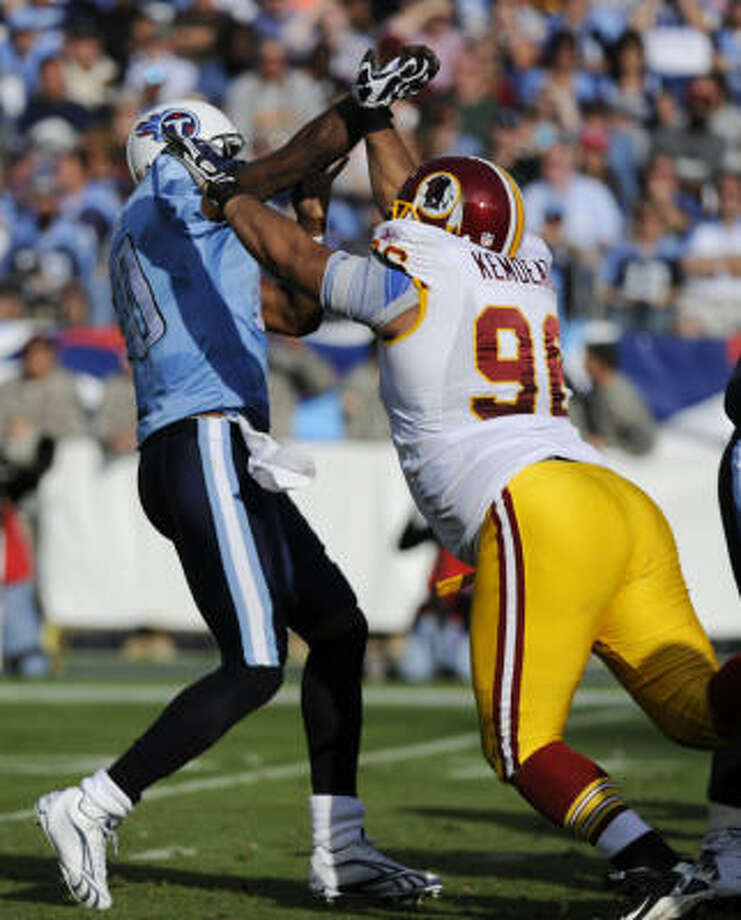 Tennessee Titans quarterback Vince Young, left, injures his right hand as he is hit by Washington Redskins defensive tackle Maake Kemoeatu in the third quarter on Sunday. Photo: Frederick Breedon, AP