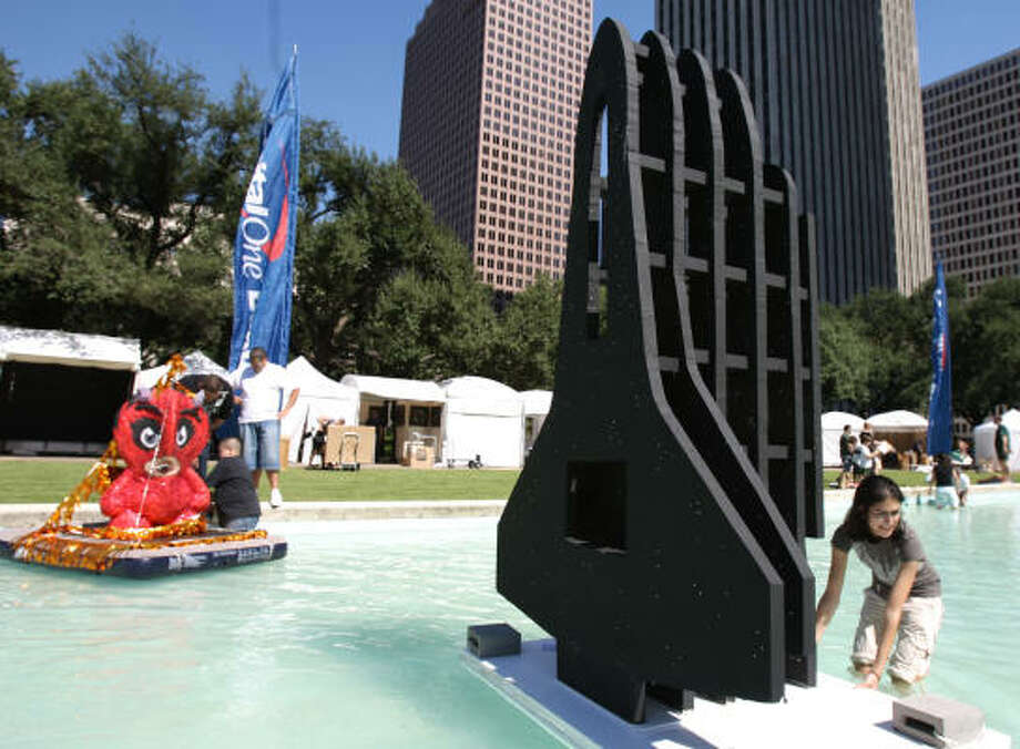 Arpi Girgorian, 17, right, of Awty International School, floats her Shuttle II masterpiece as Cyruss Pilgrim and Joey Zuniga launch their Little Dare Devil float at the Reflection Pool in preparation for this weekend's Annual Bayou City Art Festival Downtown. Photo: Julio Cortez, Chronicle