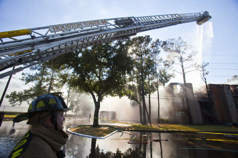 Houston firefighters battle an apartment fire Wednesday at the Driscoll Place Apartments. Two buildings were damaged and contained 48 apartment units, 37 of which were occupied by families. Photo: Eric Kayne, Chronicle