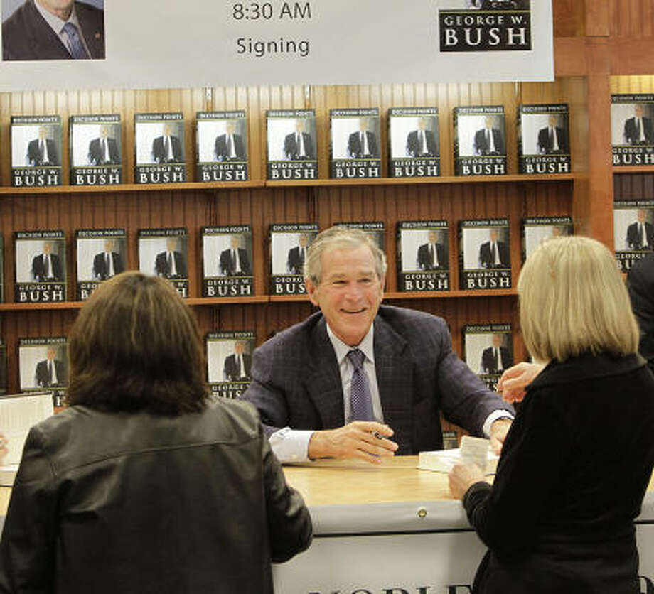 Former President George W. Bush signs copies of his memoir, Decision Points, at a bookstore in Houston. Photo: Julio Cortez, Chronicle