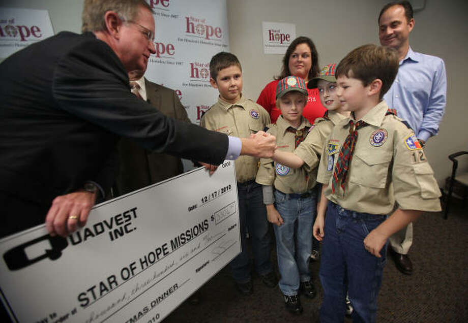 Star of Hope CEO Hank Rush shakes hands with Seth Clark, 10, and thanks him and fellow Cub Scouts Grant Goebel, 10, Garrett Parr, 10, and Dalton Burrouws, 9, as they present him with a check for $3,306, which will provide 2,028 Christmas dinners for homeless people at Star of Hope. Photo: Mayra Beltran, Houston Chronicle