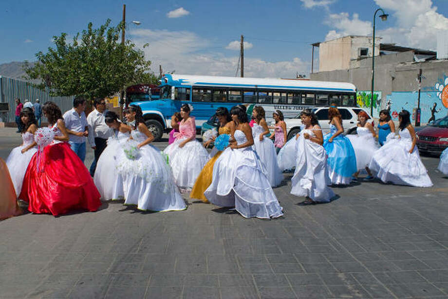 In donated gowns and with hair and makeup in place, 15-year-olds from the poorest parts of Mexico's Ciudad Juarez were given the chance to put aside their city's bloody drug violence and enjoy a cultural milestone Saturday. Photo: Keith Dannemiller, For The Chronicle