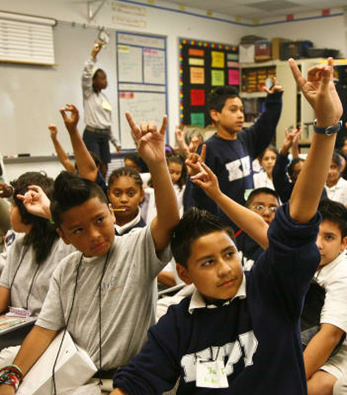 Sixth-graders raise their hands in response during a summer session class Monday at KIPP Academy. KIPP touted results of a study that dismisses questions about KIPP's methods.