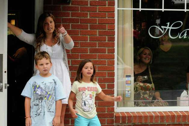 "Stylist Alexadra Bethow, left, with 8-year-old T.J. Olsen and 6-year-old Olivia Wilson, watch from Studio Orlo Salon as actor Ryan Gosling works on ""The Place Beyond The Pines"" filming at the 1st National Bank of Scotia in Niskayuna, NY, on Wednesday, Aug. 3, 2011.( Michael P. Farrell/Times Union) Photo: Michael P. Farrell"