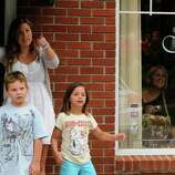 """Stylist Alexadra Bethow, left, with 8-year-old T.J. Olsen and 6-year-old Olivia Wilson, watch from Studio Orlo Salon as actor Ryan Gosling works on """"The Place Beyond The Pines"""" filming at the 1st National Bank of Scotia in Niskayuna, NY, on Wednesday, Aug. 3, 2011.( Michael P. Farrell/Times Union)"""
