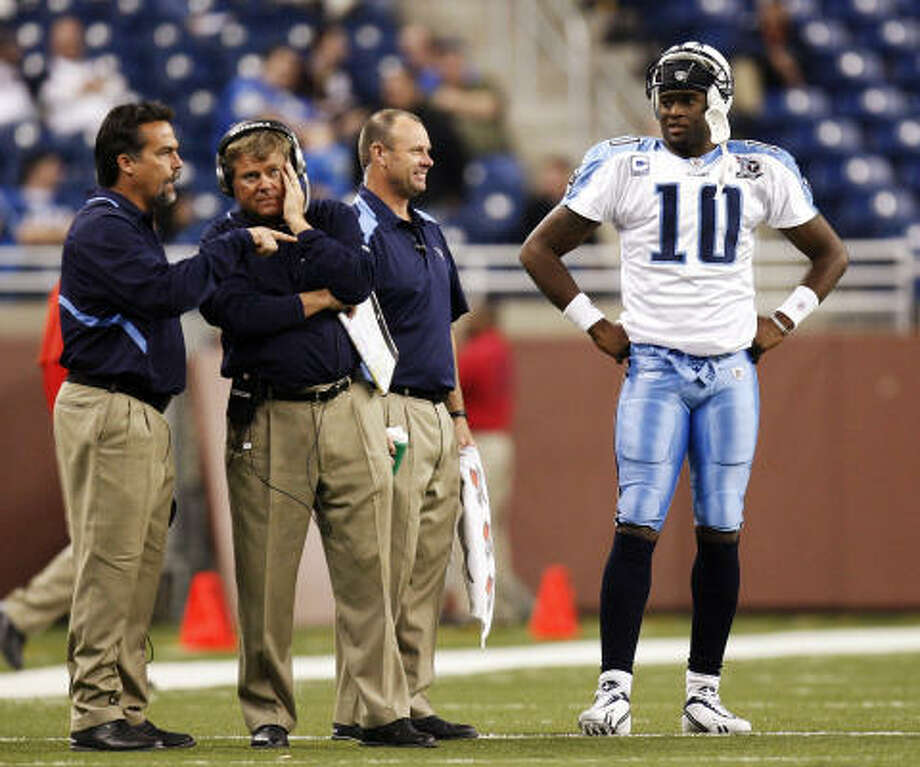Titans offensive coordinator Mike Heimerdinger listens to head coach Jeff Fisher while quarterback Vince Young talks to trainer Brad Brown. Photo: Gregory Shamus, Getty Images
