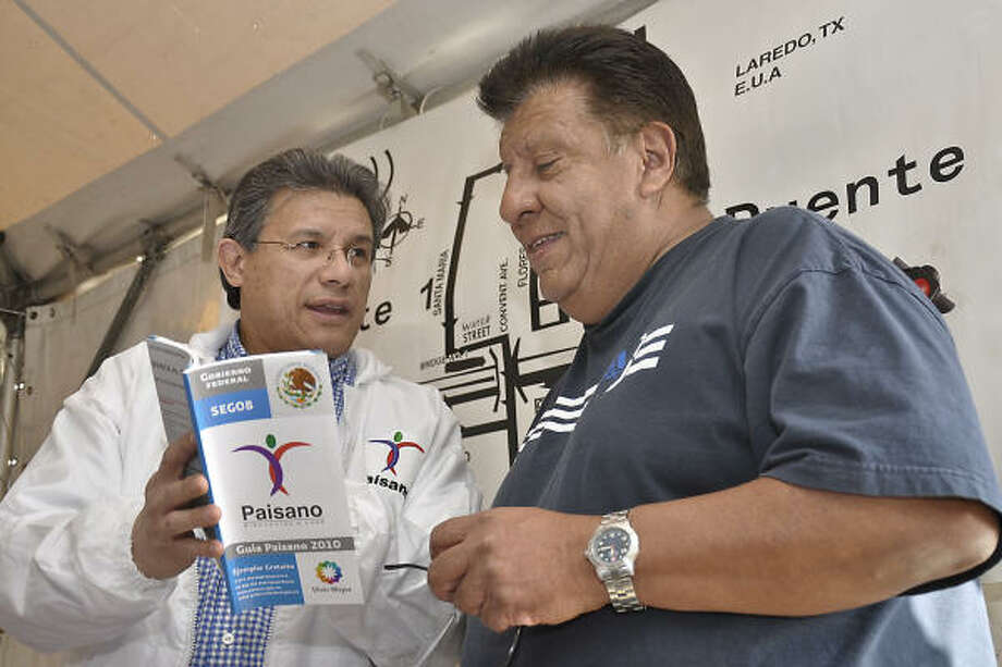 Abraham Ramirez, right, who is traveling from Arkansas to Mexico, gets some assistance from Mario Perez, of the Paisano Program in Houston, on Friday at the paisano rest stop on Interstate 35. Photo: Cuate Santos, Laredo Morning Times