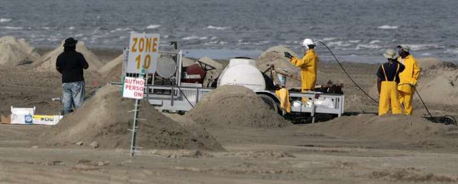 Oil cleanup workers use pressure washers Friday as they clean up the beach on Grand Isle, La., as coastal residents remained hopeful BP had its runaway well under control. Photo: Dave Martin, Associated Press