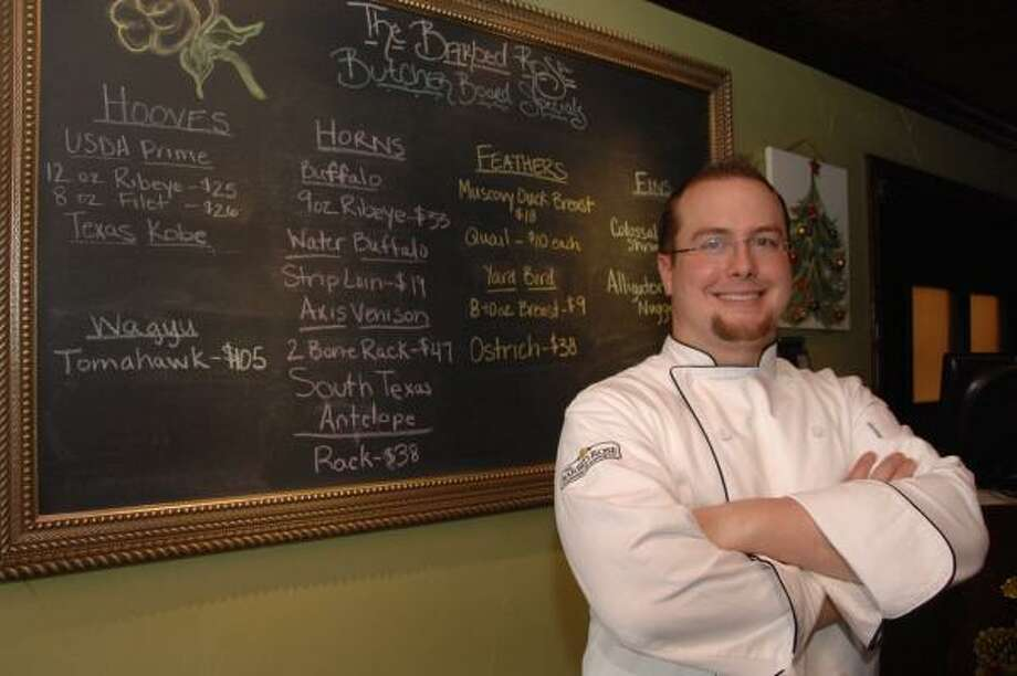 AT WORK: Chef Jason Chaney stands by the menu at his recently opened restaurant, the Barbed Rose Steakhouse and Seafood Company, 113 E. Sealy in Alvin. Photo: Jimmy Loyd, For The Chronicle