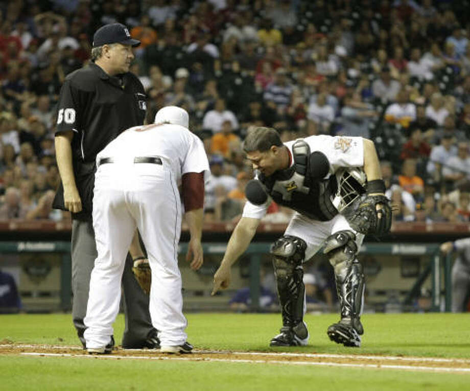 Astros catcher Humberto Quintero tries to convince home plate umpire Paul Emmel that the ball is foul on a bunt in the ninth inning. Photo: Nick De La Torre, Houston Chronicle