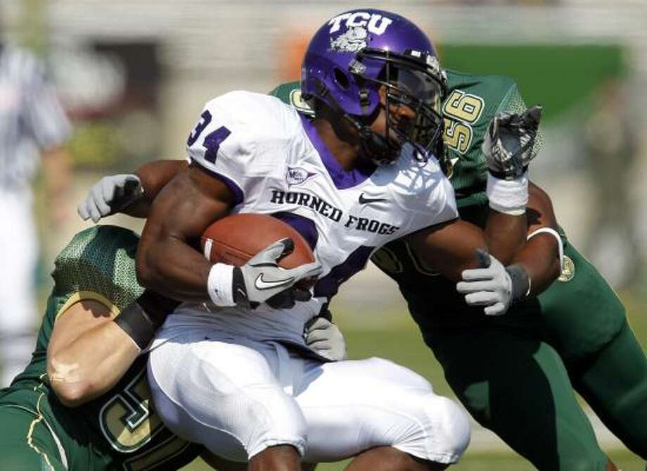 TCU running back Ed Wesley is tackled by Colorado State linebacker Ricky Brewer (56) and Alex Williams (51) during the first quarter. Photo: Jack Dempsey, AP