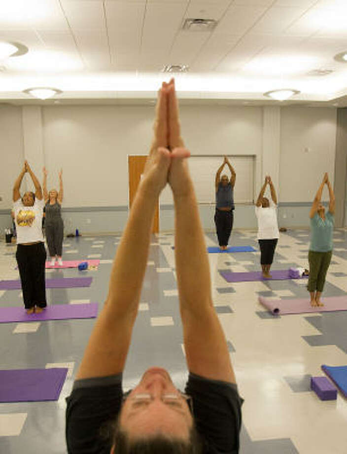 Kay Westcott, center, leads a group in yoga at the William A. Vinson HPL Express and Neighborhood Library as a part of the Houston Public Library's Stress Buster program. Photo: Johnny Hanson, Chronicle