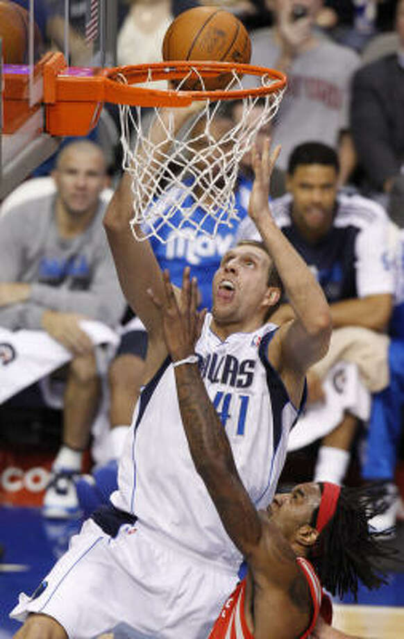 Mavericks forward Dirk Nowitzki looks to score two of his 20 points as Rockets forward Jordan Hill defends on Monday night. Nowitzki played only 29 minutes in the victory. Photo: LM Otero, AP