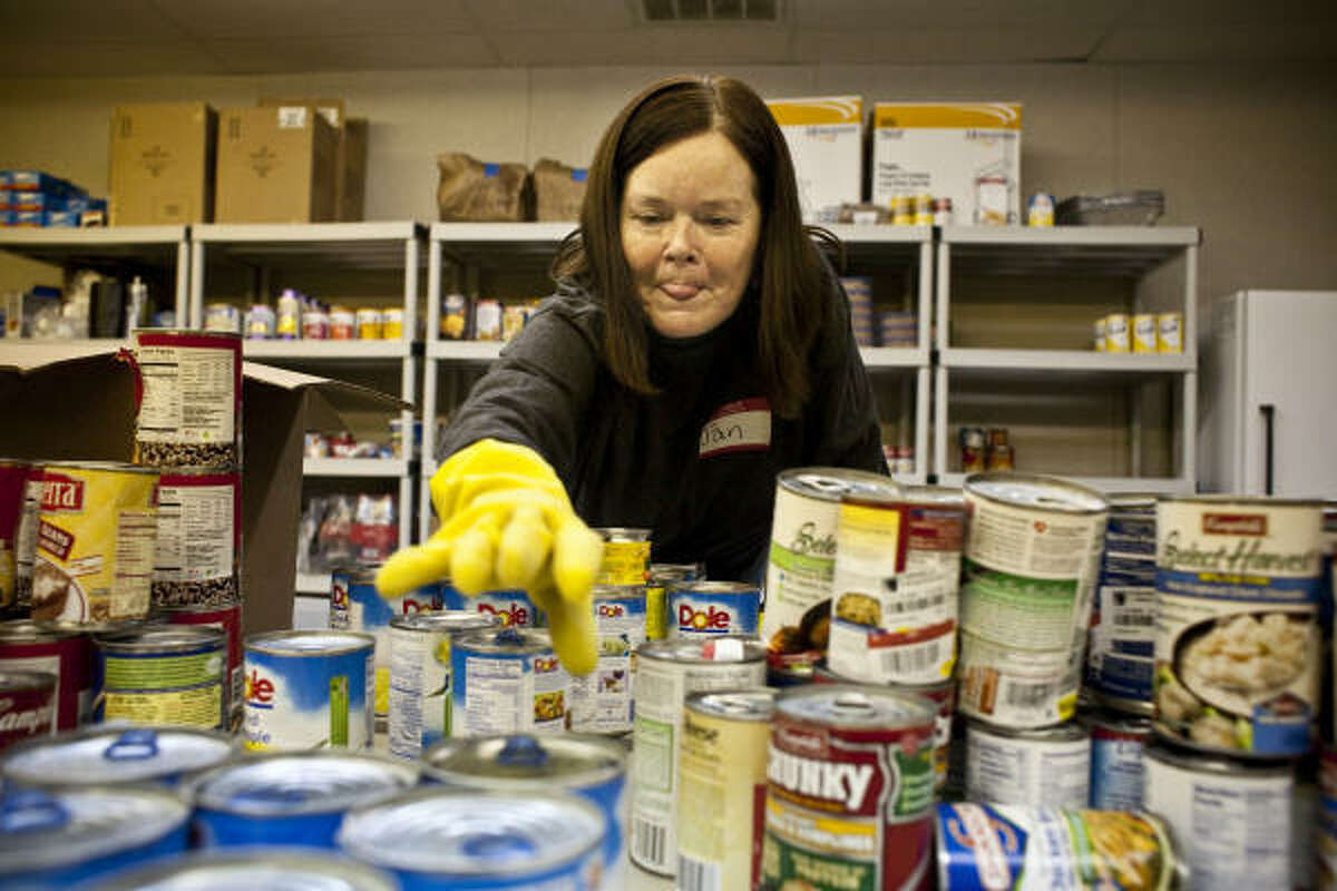 Jan Holly, a volunteer and client, arranges canned goods at Bethel's Heavenly Hands Ministry, one of more than a dozen food pantries in the region that responded to a survey on need.