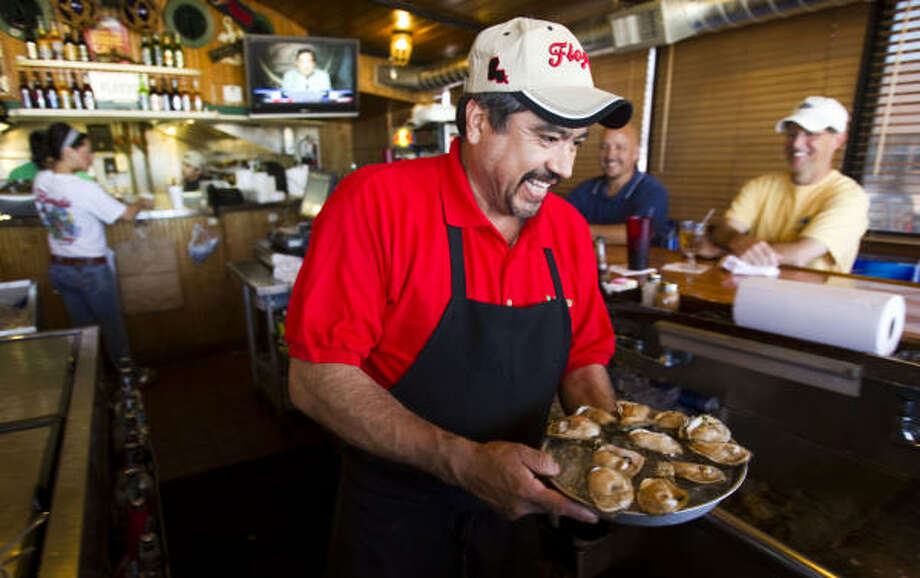 Manuel Pena serves customers at Floyd's Cajun Seafood restaurant at NASA Road 1 and the Gulf Freeway last week. A shortage of Gulf oysters and other seafood may be ahead. Photo: Brett Coomer, Chronicle