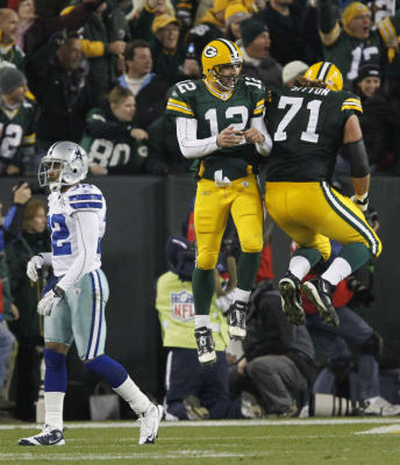 Packers quarterback Aaron Rodgers (12) celebrates with Josh Sitton in front of the Cowboys' Orlando Scandrick after Rodgers threw a touchdown pass during the second half. Photo: Mike Roemer, AP