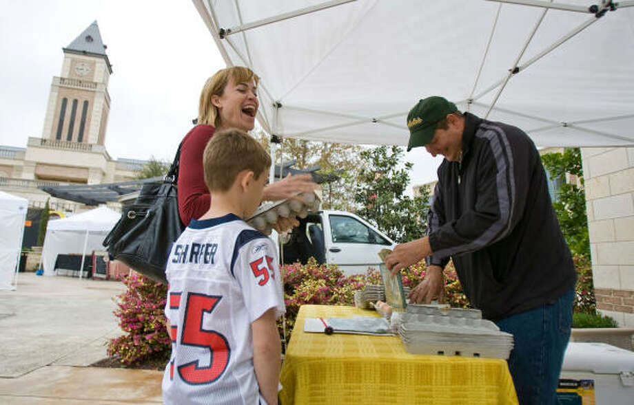 Leah Crawford jokes with Dustin Hoeinghaus of Dustin's Eggs as she buys fresh free-range eggs during a farmers' market. LaCenterra at Cinco Ranch uses its public spaces to hold community events, and it has the farmers' market on Saturdays. Photo: Nick De La Torre :, Chronicle